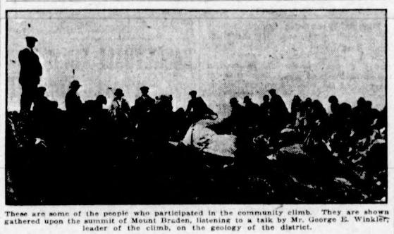 Dark photo of group gathered on the summit of Mount Braden.